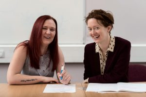 Two women smile and laugh as they complete a form